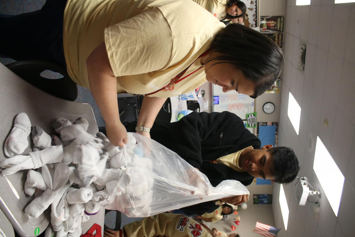 CARING. Sarah Dudley, StuCo co-adviser, and junior Ivan Sanchez, president of StuCo, empty out a donated bag of socks