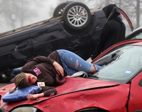 Senior Katelyn Finley lies across the hood of a vehicle after being thrown through the windshield during a simulated car wreck as part of the Shattered Lives program Wednesday, Feb. 27, 2019, at Caney Creek High School.