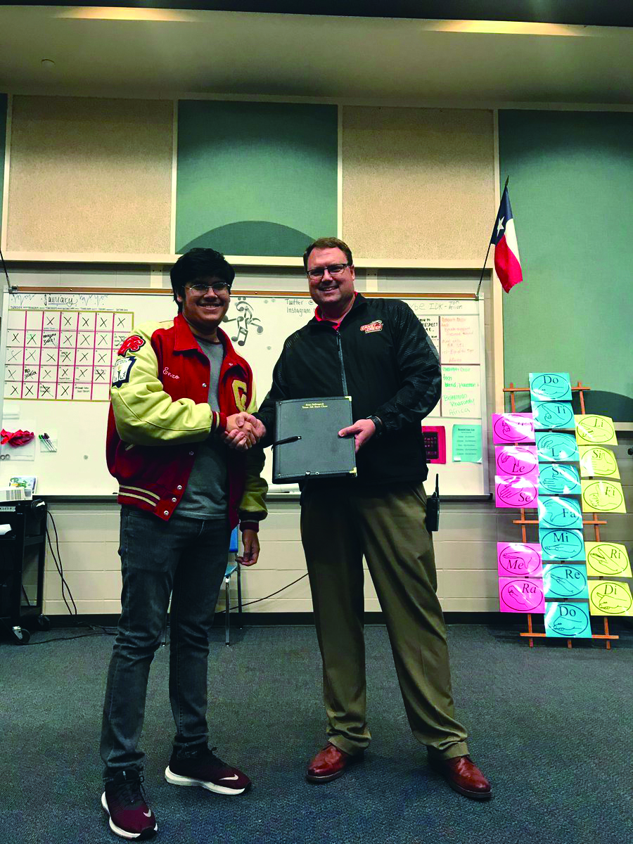 All-STATE. Dr. Jeffrey Stichler hands senior Enzo Bellingardi a folder that he used in the Texas all-state mixed choir.