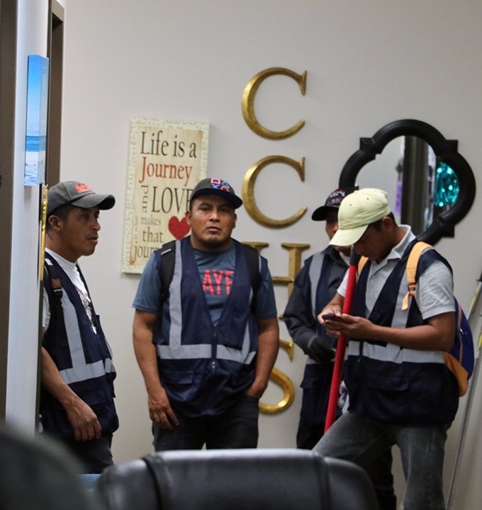 Contractors meet before ripping out carpet in the councilors office.
