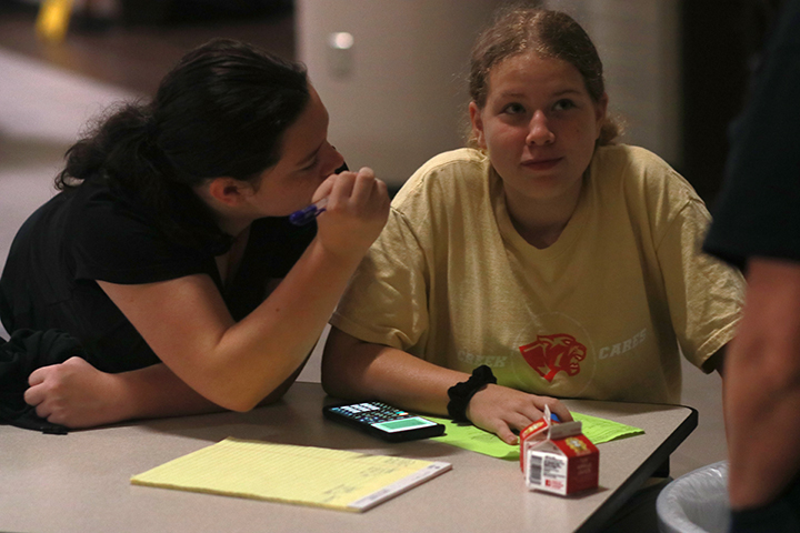 Students work on homework and talk with teacher Kelly Goodwin while waiting on rides home.