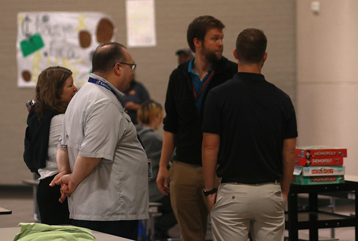 Teachers Leigh Anne Treistman, Richard Nance, Gannon Rust, and Ray Sweat wait in the small cafeteria.