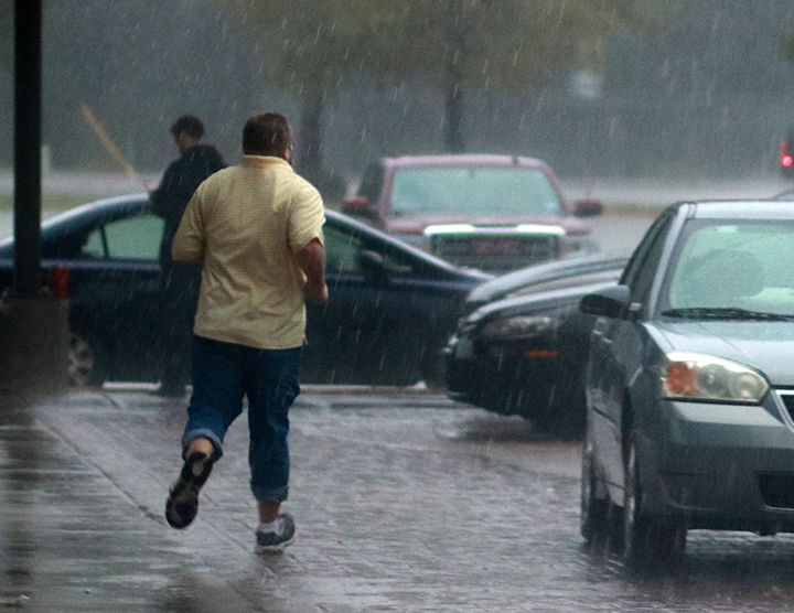 Social studies teacher Eric Tanner runs to his car, which was inches from being flooded.