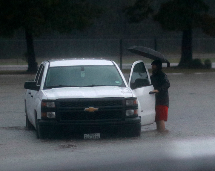 Math teacher Stephen Meine moves his truck as the water flooded the staff parking lot.