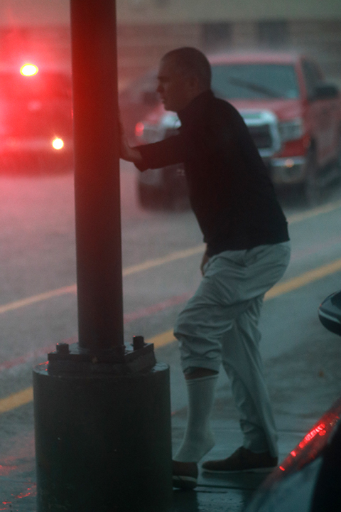 Assistant Principal Brad Milam takes off his shoes as the water rose over the sidewalk at the bus ramp.
