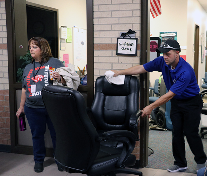 Counselor Cindy Horn and a contractor clear out the damaged counselors office.