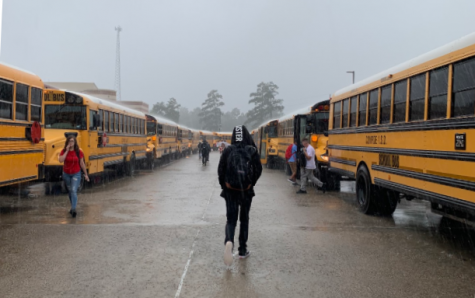 A student walks to their bus after being released five minutes early due to heavy rainfall.