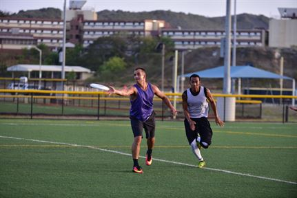 A player from the Frisbees of the 7 Seas passes to a teammate before an opponent from Netflicks & Chill can break up the play during an Ultimate Frisbee game July 19 at Cooper Field on U.S. Naval Station Guantanamo Bay, Cuba.