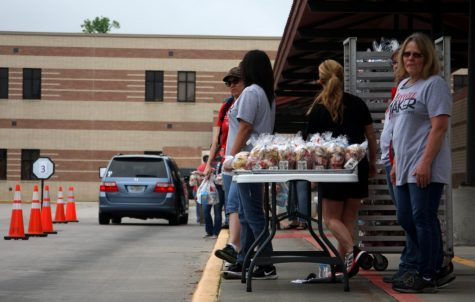 Conroe ISD employees waiting for the next car to go through with table full of meals.