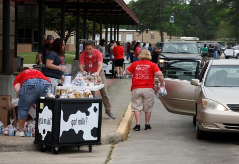 Staff members from the Caney Creek feeder zone in the middle of the rush  staff handing out food.