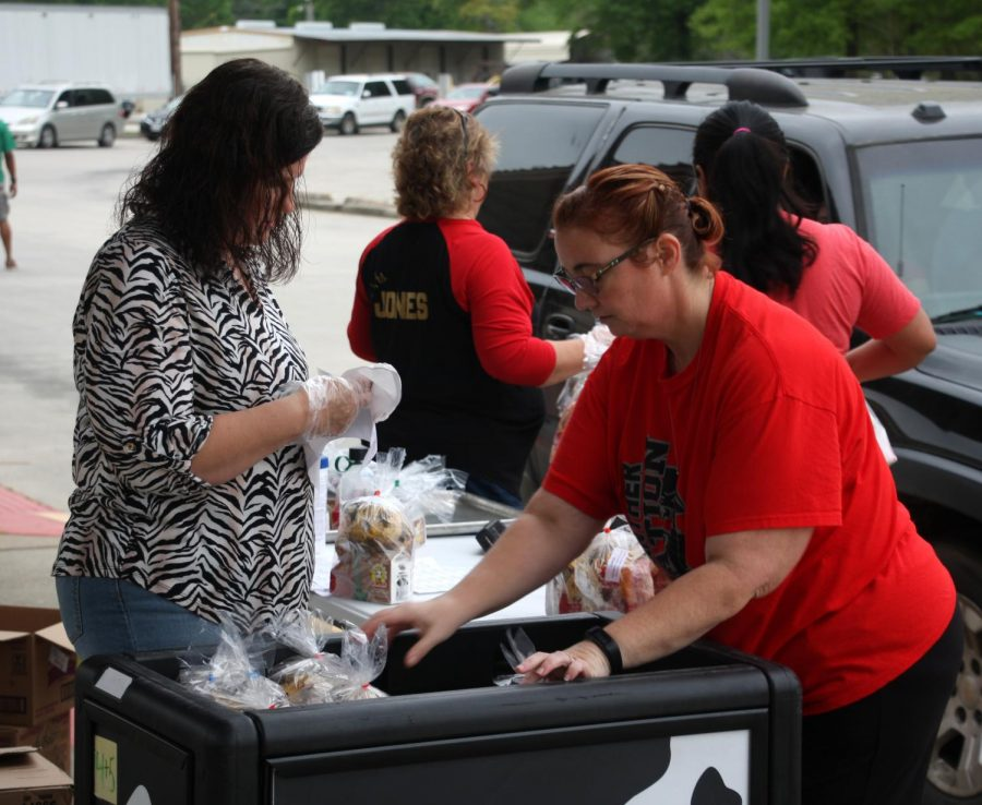 Caney Creek feeder zone employees unload breakfast and lunch bags during a curbside food distribution March 20,  soon after the district stopped in-person learning.