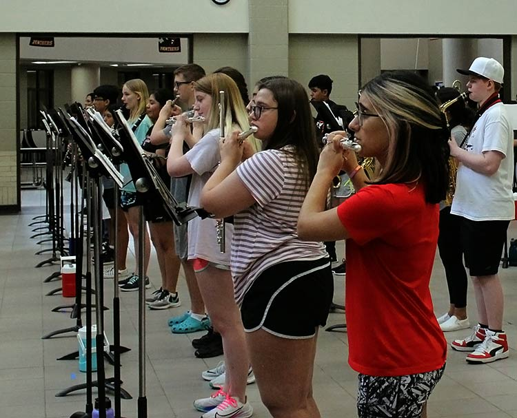 """Band students practice in the cafeteria without masks before school starts on July 28 due to the construction occurring in the school's parking lot and with less restrictions with Covid-19. Freshmen Addy Blanks said """"We had to wear a face shield while playing, and every time we had to go over rhythms we had to have a facemask."""""""